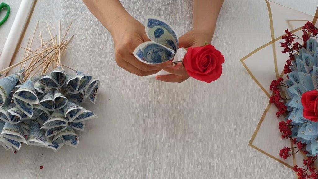 Dùng hoa hồng sáp vào giữa thanh xốp. Tiếp tục cắm các cánh hoa tiền xung quanh hoa hồng.