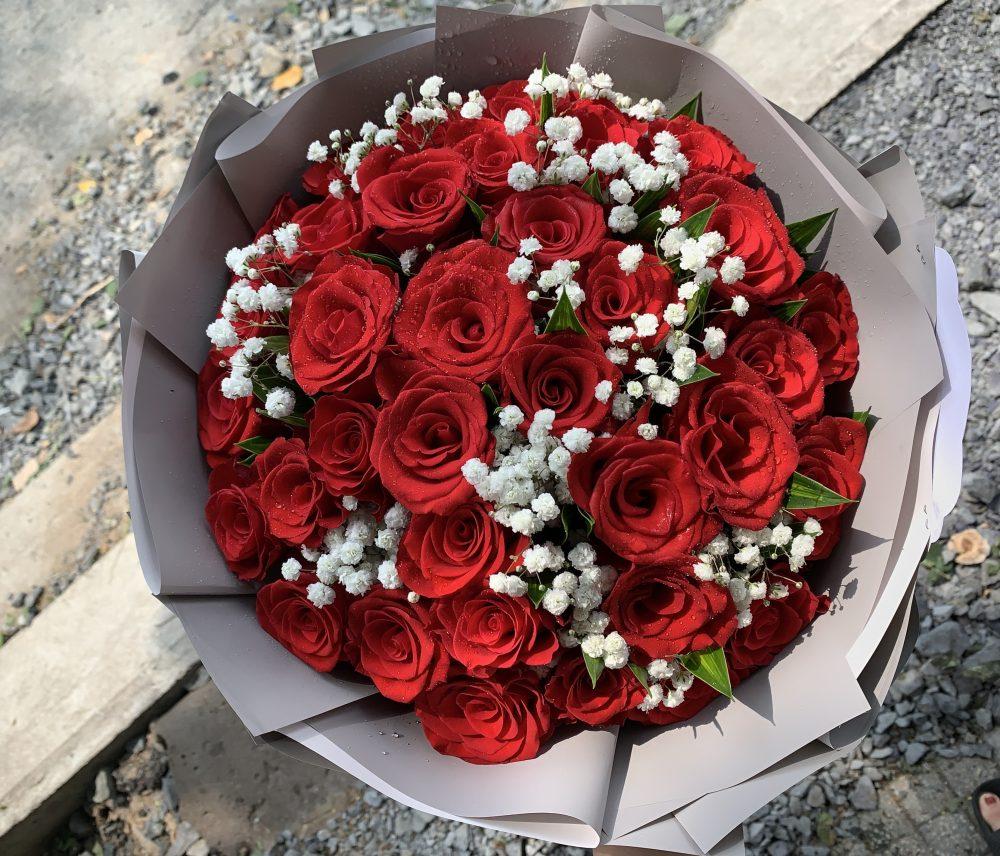 Gói giấy vào bó hoa hồng đỏ với hoa baby